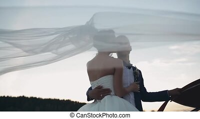 Veil waving on the wind. Bride and groom tenderly hugging on sunset. Evening of beautiful man and woman after wedding.