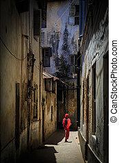 Veiled woman walking through a narrow street