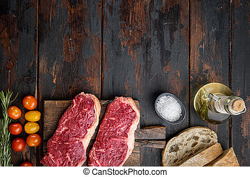 Veiny steak, marbled beef meat, on dark wooden background, top view, with copy space for text