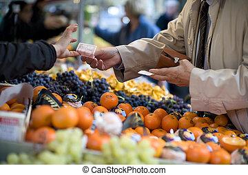 Vendor accepts payment at a street market - A man reaches ...