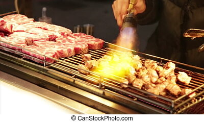 Vendor cooking beef with blowtorch at Lehua Night Market in the Yonghe District