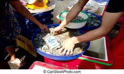 Vendor Moves Shrimp Into Basket for Customer Waiting to Buy Them.