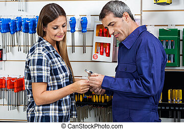 Vendor Showing Wrench To Customer In Shop