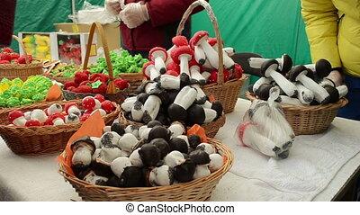 vendor sweet market - vendor puts in a bag doughy mushrooms...