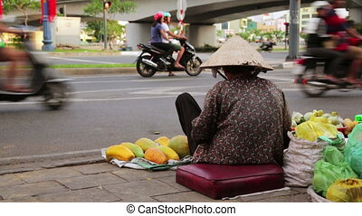 Vendor woman sitting and selling fruits on heavy hanoi traffic