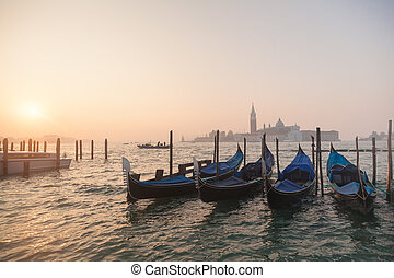 Venetian gondolas at sunrise in venice