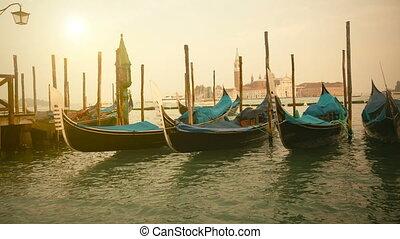 Venetian gondolas at sunrise tied near the pier on San Marco...