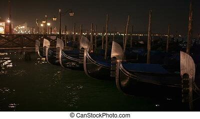 Venetian gondolas tied near the pier at night on San Marco...