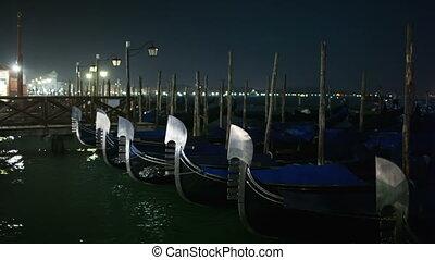 Venetian gondolas tied near pier - Venetian gondolas tied...