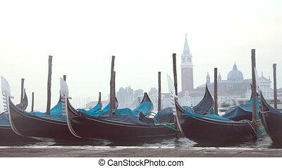 Venetian gondolas tied near pier