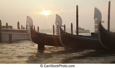 Venetian gondolas tied near the pier on San Marco square at...