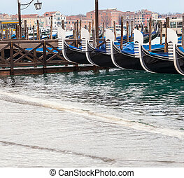 ypical Venetian gondolas with high tide that causes the famous event of high water in Venice, Italy.