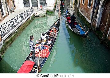 venetian gondolas with tourists sailing the waterways of...