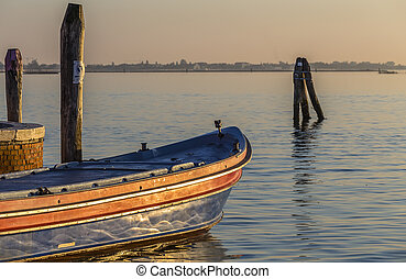 Venetian lagoon and fragment of a boat in the rays of the setting sun