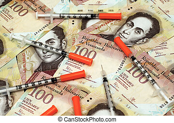 Venezuelan currency close up with hyperdermic needles