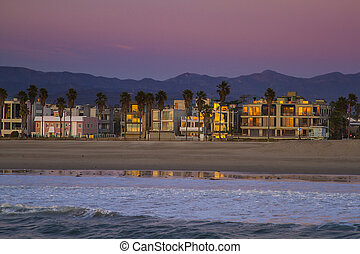 houses on the venice beach at the end of a sunset
