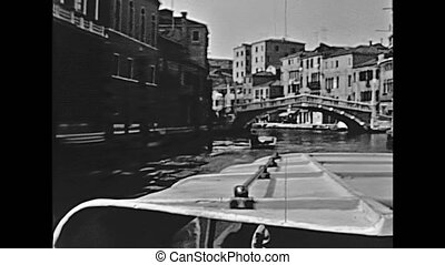 Historical boat tour on Cannaregio canal, lower view of Delle Guglie, Bridge of Spires, one of the main bridges of Venice in Italy, Italian city of Unesco Heritage. Historical restored footage on 1960