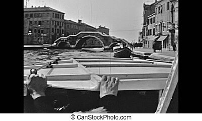 Historical boat tour on Cannaregio canal, person view of Bridge of Three Arches, one of the main bridges of Venice in Italy, Italian city of Unesco Heritage. Historical restored footage on 1960.