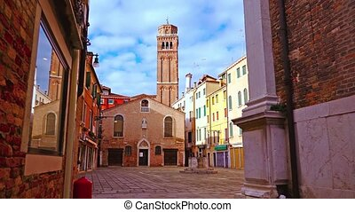 Deserted Italian Venice city square with terracotta brick chapel and high bell tower among colorful buildings under blue sky