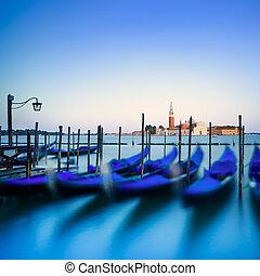 Venice, gondolas or gondole on a blue sunset twilight and San Giorgio Maggiore church landmark on background. Italy, Europe.