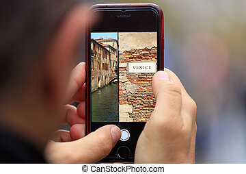 Venice in Italy picture appears on tablet, smartphone in man's hands. Blurred background