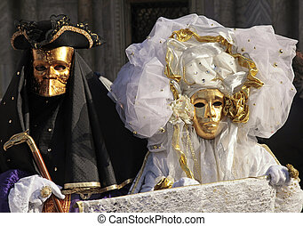 masked persons in costume on San Marco Square during the...