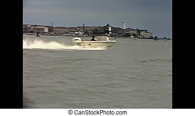 Historical touristic boat tour from Venezia to Murano island, with San Michele in Isola church on the horizon in venetian lagoon. Amateur archive footage on 1967s.