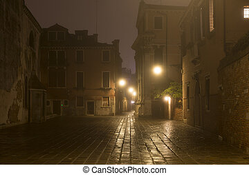Venice street without people with night fog, Italy