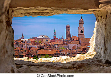 Venice towers and rooftops view through stone window