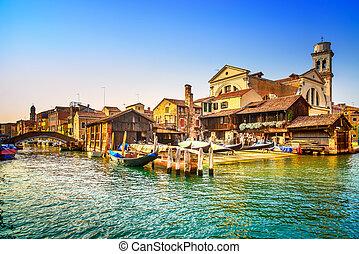 Venice, water canal, bridge and gondolas or gondole depot on sunset. Italy, Europe.