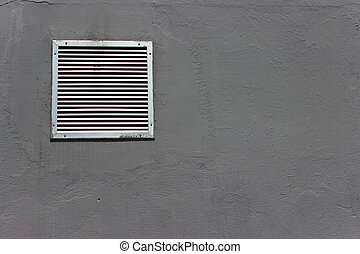 Vent window on gray concrete wall