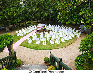 Venue for a wedding with chairs for guests and trees around.