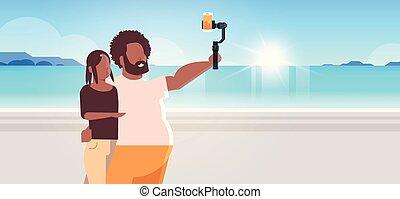 verão, conceito, foto, selfie, smartphone, mar, retrato, paisagem, ficar, férias, câmera, segurando, praia, mulher, par, vara, fundo, horizontais, homem, levando, litoral, junto, americano, africano
