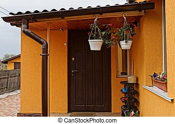 veranda of a brown private house with a closed door and flowerpots