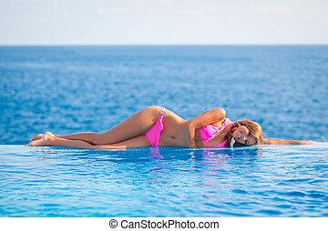 verano, mujer sunbathing, en, infinito, piscina