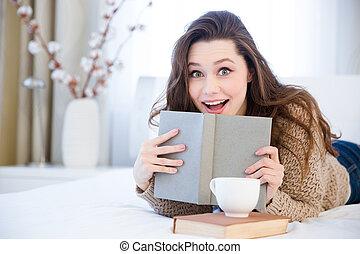 verbaasde vrouw, het liggen op het bed, en, het boek van de...