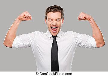 verborgen, possibilities., mooi, jonge man, in, hemd en meren, kijken naar van fototoestel, en, het tonen, zijn, biceps, terwijl, staand, tegen, grijze , achtergrond
