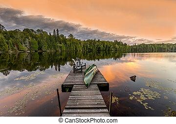 verde, canoa, y, sillas, en, un, muelle, en, ocaso