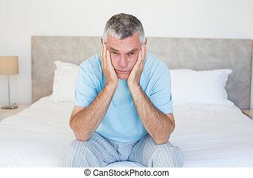 verdrietige , hogere mens, zitting op het bed