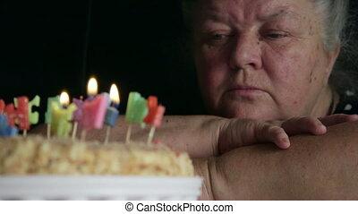 verdrietige , oude vrouw, kijken naar, verjaardagstaart, met, brief, kaarsjes, gelukkige verjaardag