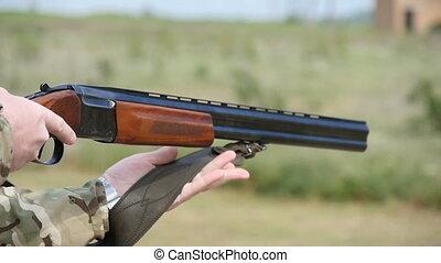 Verical double barrel shortgun used bya man for skeet shooting in slow motion