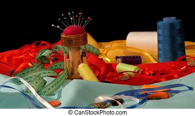 Vericolored threads, needles, meter on bright blue, yellow and red clothes, black background, rotation