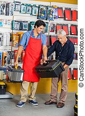 verkäufer, assistieren, mann, in, auswählen, werkzeugkasten, an, kaufmannsladen