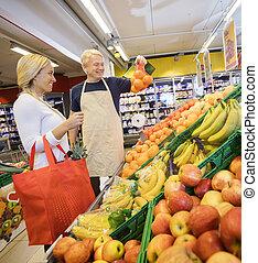 verkäufer, ausstellung, orangen, zu, weibliche , kunde, in, lebensmittelgeschäft