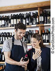 verkäufer, ausstellung, weinflasche, zu, glücklich, weibliche , kunde