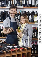 verkäufer, besitz, digital tablette, während, kunde, mit, weinflasche