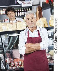 verkäufer, stehende , verschränkte arme, während, kollege, arbeiten, counte