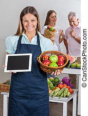 verkäuferin, besitz, digital tablette, und, früchte, korb