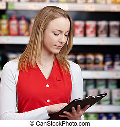 verkäuferin, lesende , prüfliste, auf, klemmbrett, in, lebensmittelgeschäft
