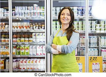 verkäuferin, mit, verschränkte arme, stehende , gegen, kühlschrank